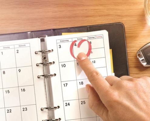 Finger zeigt auf Termin im Terminkalender