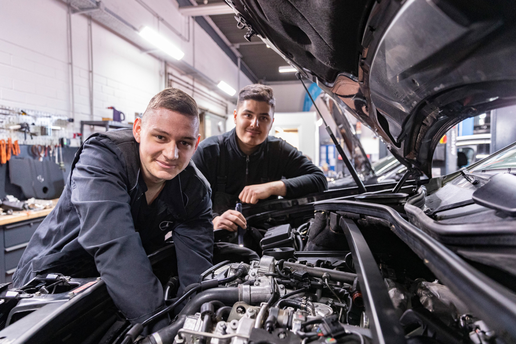 Mechaniker an offener Motorhaube von Mercedes in Werkstatt